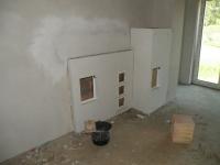 Topná stěna s otvory do prvního pokoje v patře, kde je zaústění do komína.