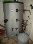 Akumulační nádrž v technické místnosti s regulačními topenářskými prvky.